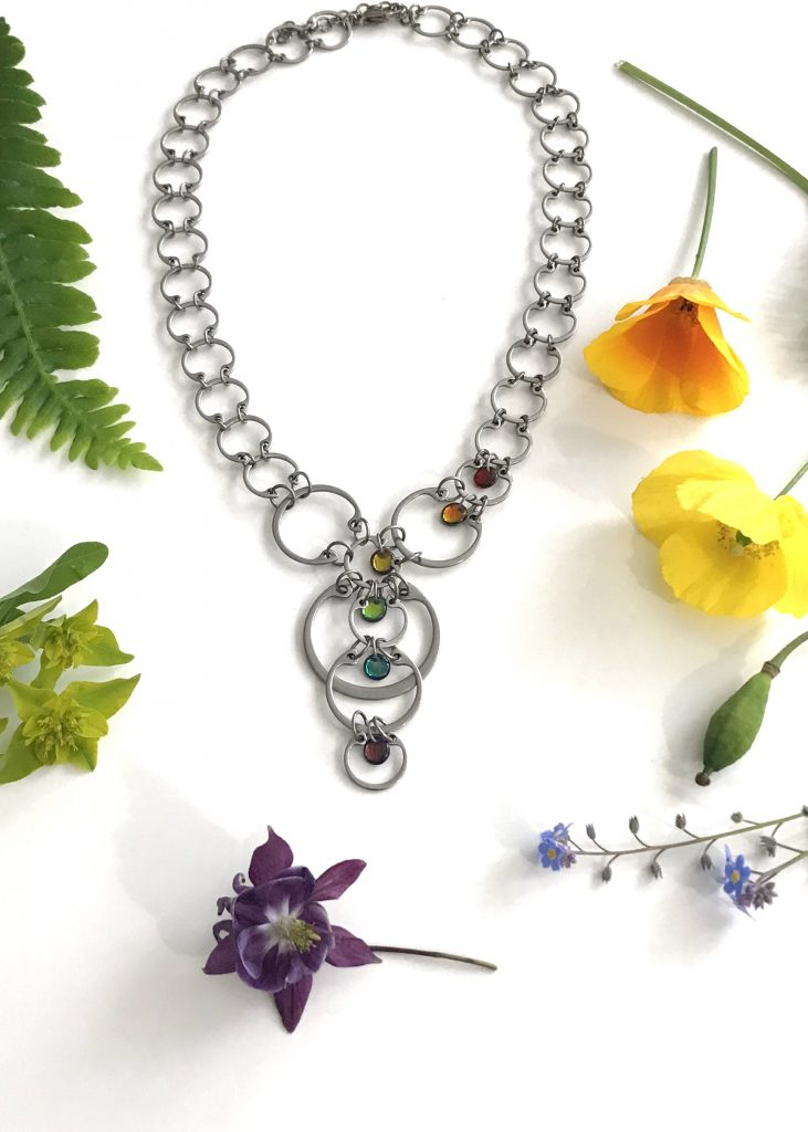 Cascading Rainbow Circles Necklace from Wraptillion's Industrial Glass collection, shown with a rainbow of flowers