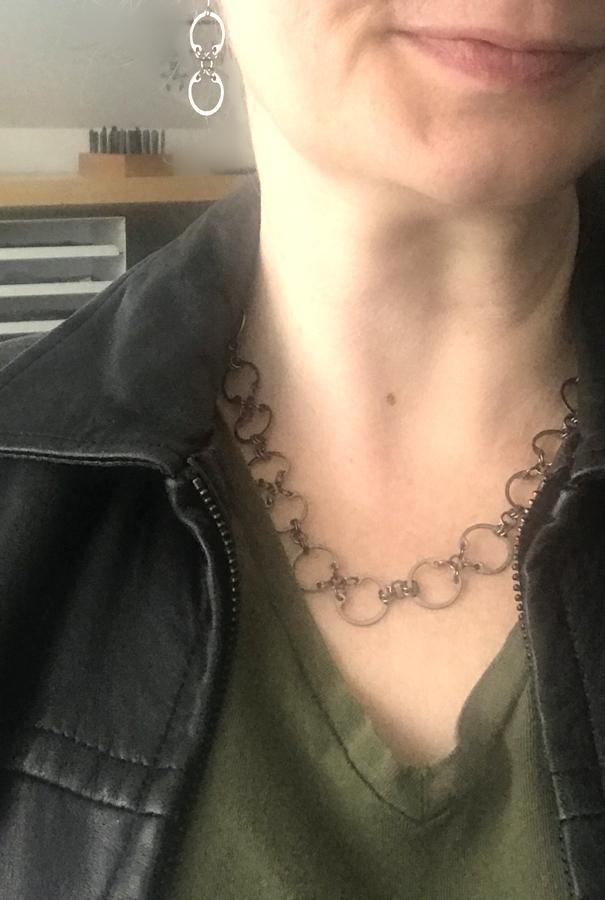 Baseline CXC Earrings and Baseline CXC Necklace by Wraptillion (modeled studio snapshot, black leather jacket, khaki green v-neck tee)