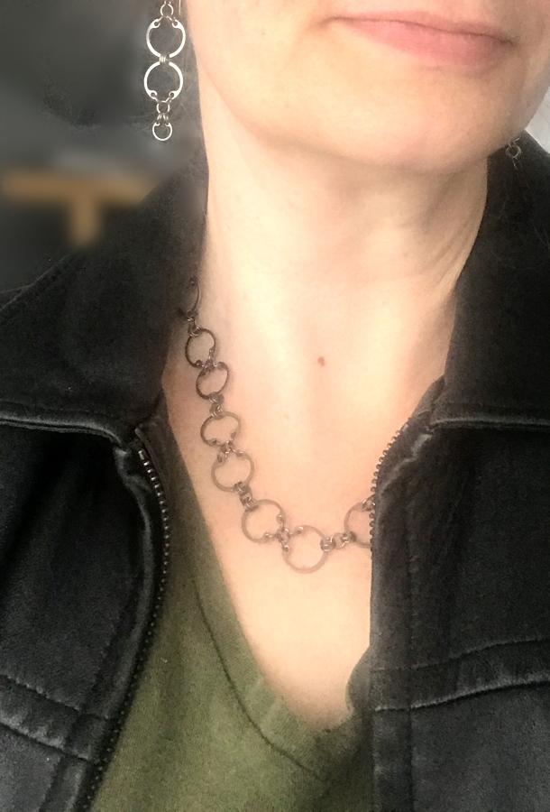 C=Cxc Earrings and Baseline CXC Necklace by Wraptillion (modeled studio snapshot, black leather jacket, khaki green v-neck tee)