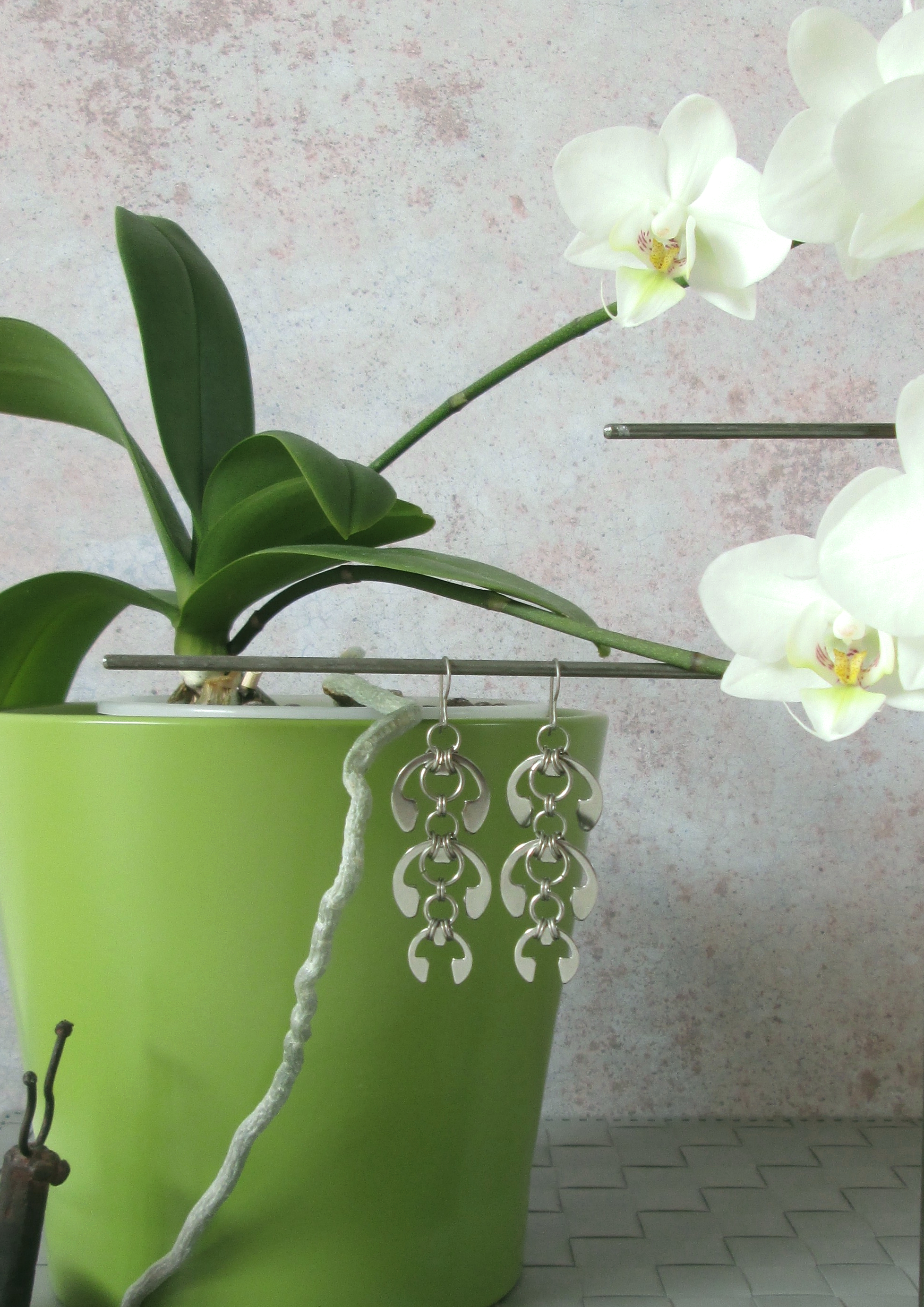 Vignette of a white phalaeonopsis orchid in a green pot with Wraptillion's Laburnum Earrings and the head of a metal snail figuerine.
