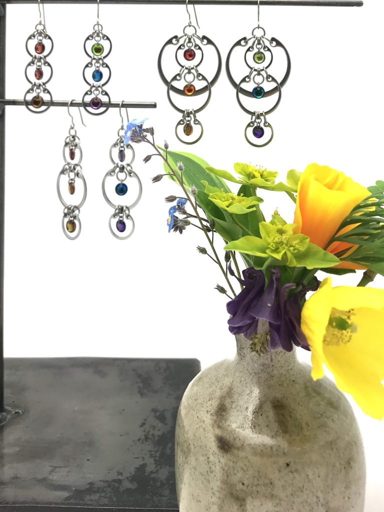 A rainbow of flowers in a small vase in Wraptillion's studio, with jewelry from the Industrial Glass Rainbows collection: poppies, columbine, euphorbia, hosta, forget-me-nots.