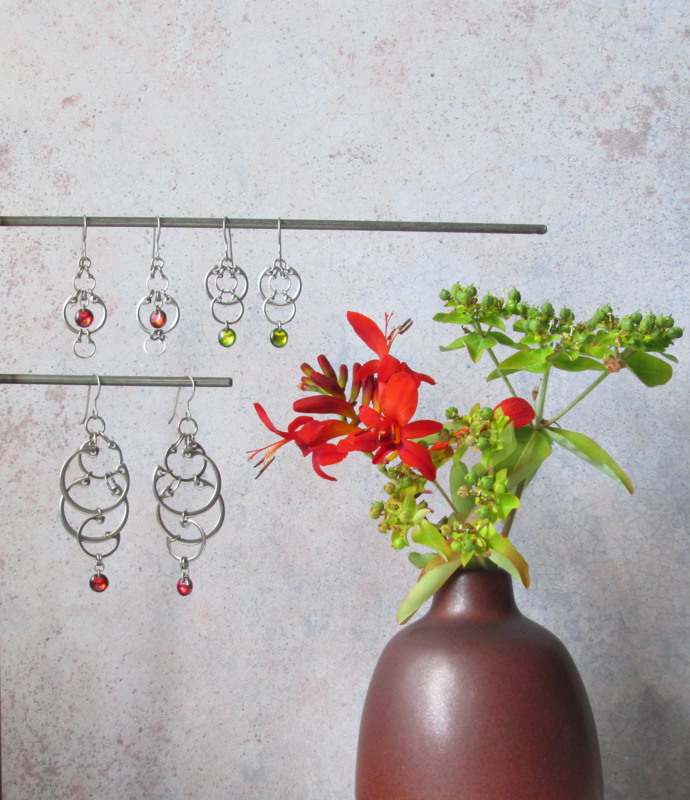 Red crocosmia flowers and green euphorbia buds with red and green earrings from Wraptillion's Industrial Glass collection.
