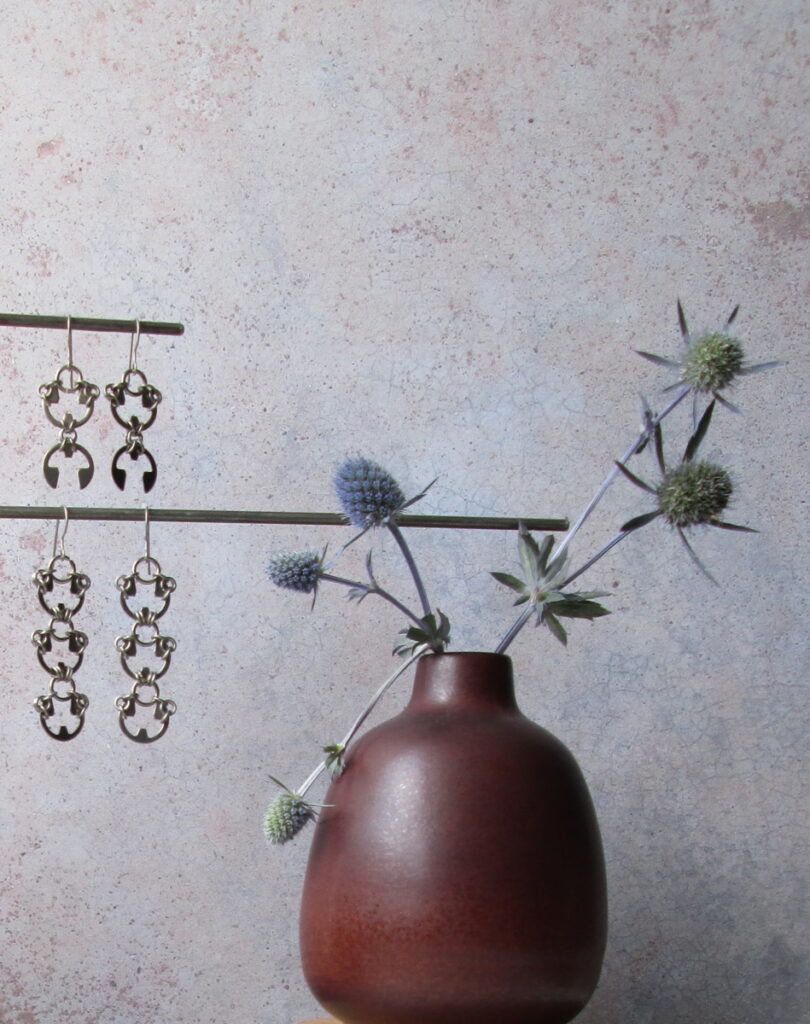 Blue sea holly flowers in a small modern bud vase, with Wraptillion's Scarab Earrings and Lotus Earrings.