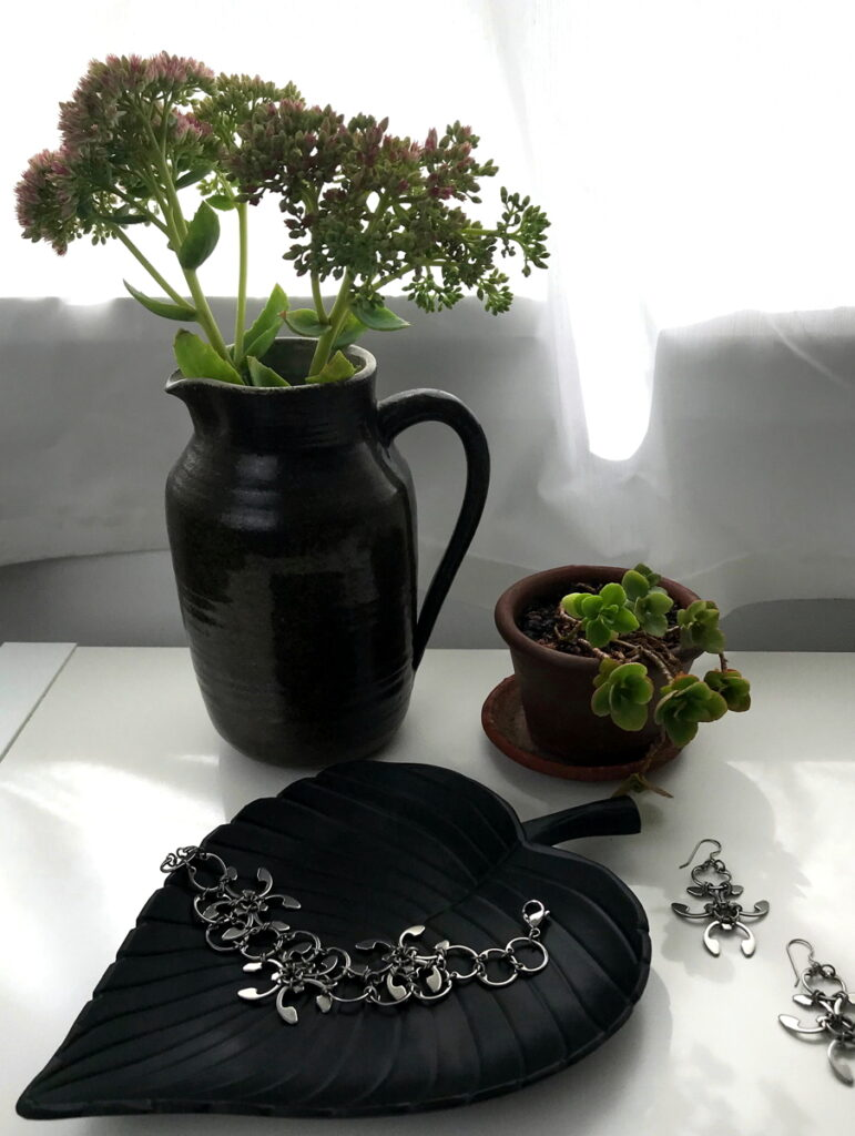 Sedum 'Autumn Joy' in a vase with a small potted sedum in Wraptillion's studio, with the Garland Bracelet and Earrings.
