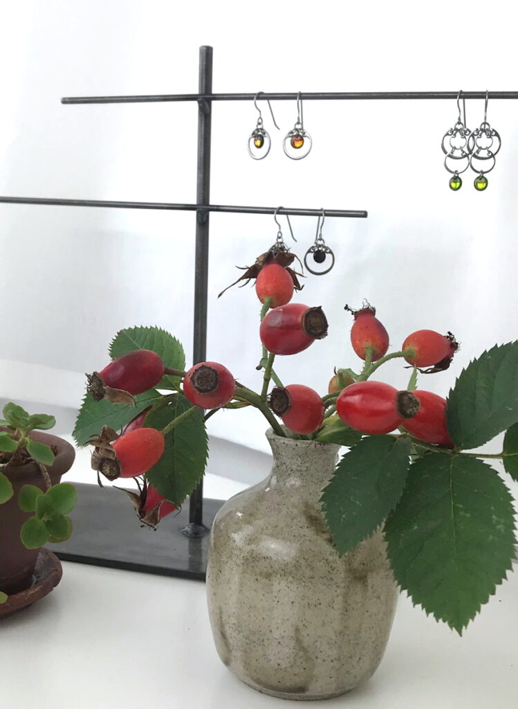 Rosa alba hips and a small potted sedum on Wraptillion's desk, with earrings from the Industrial Glass collection.