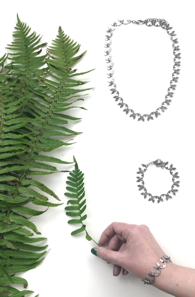 Cut sword fern fronds, shown in a flat lay with the Fern Necklace and Fern Bracelet. A hand wearing the Fern Bracelet holds another fern frond.