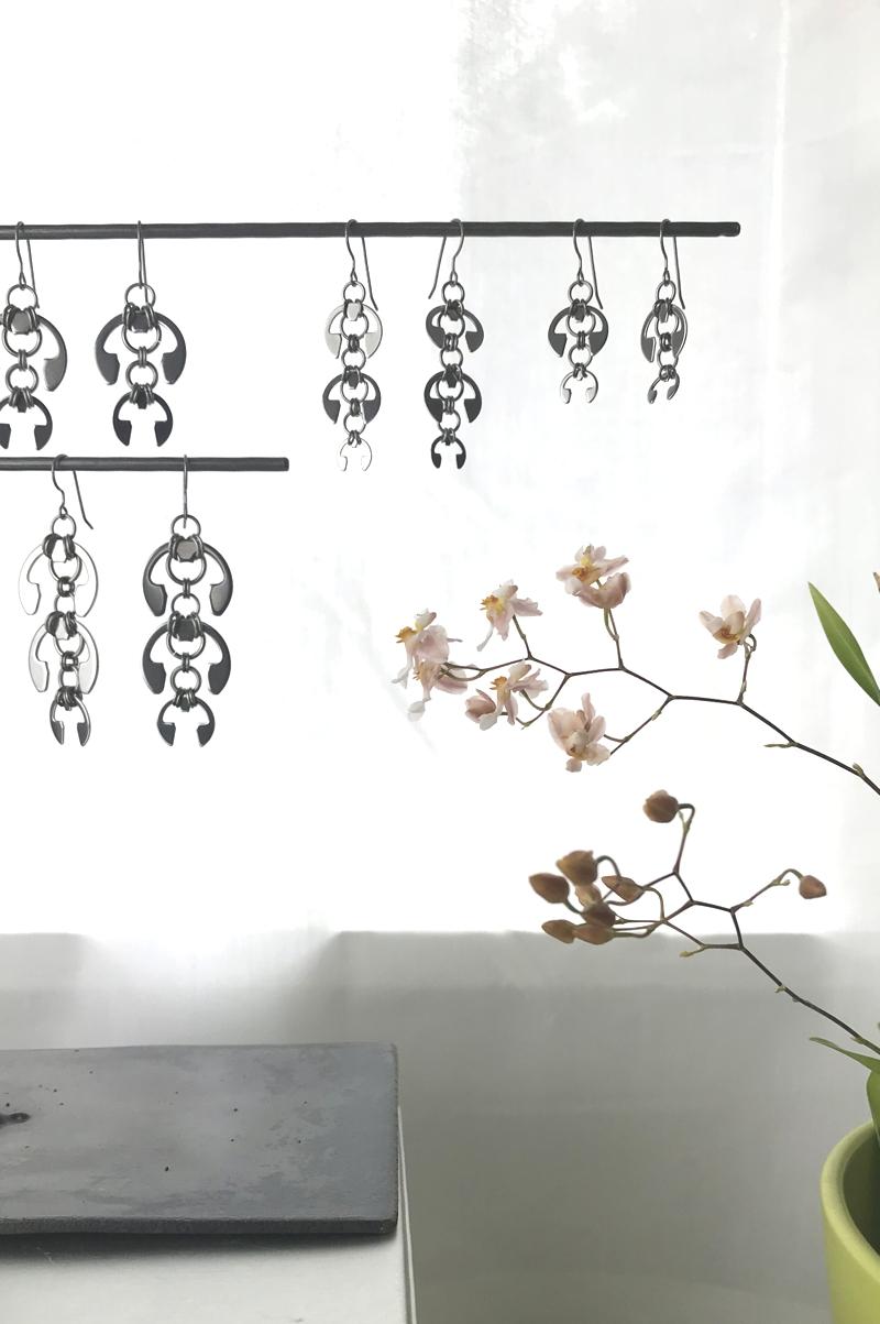 Wraptillion's Hops Earrings, Laburnum Earrings, Long Fuchsia Earrings, and Short Fuchsia Earrings, on a jewelry stand with orchid Oncidium 'Tsiku Marguerite' in a studio.