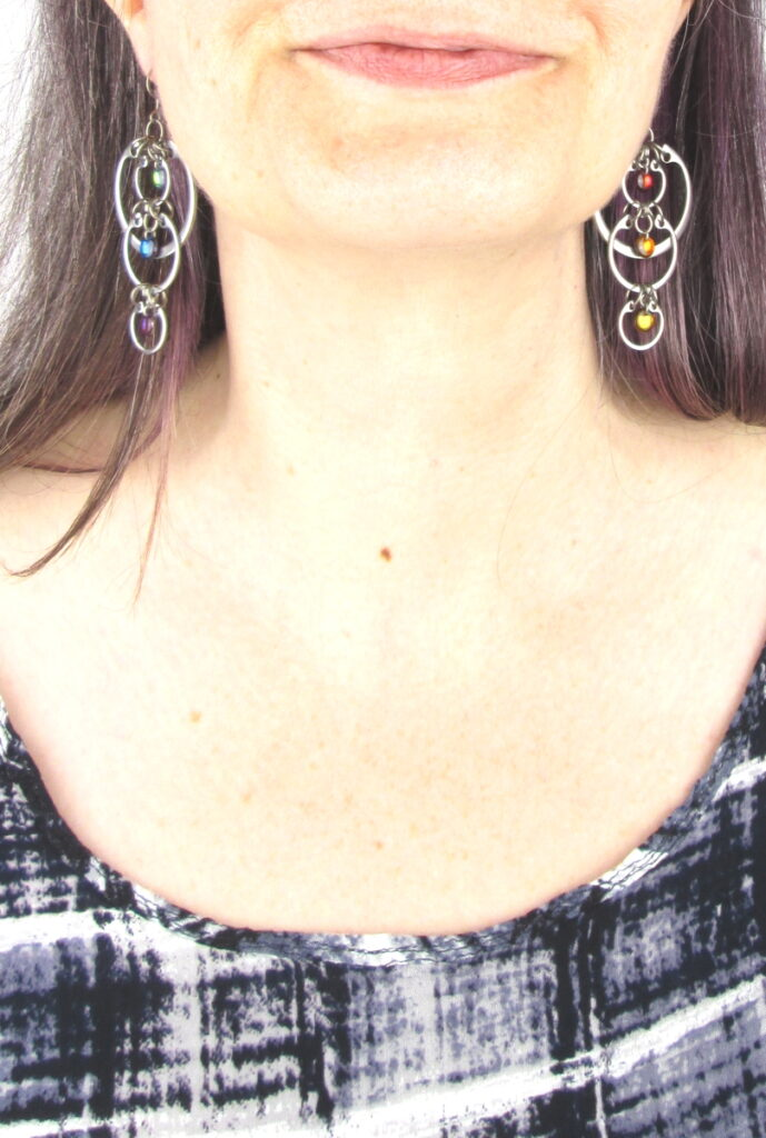 Cropped photo of artist Kelly Jones wearing Wraptillion's modern linked circle Cascading Rainbow Earrings with a black and white top.
