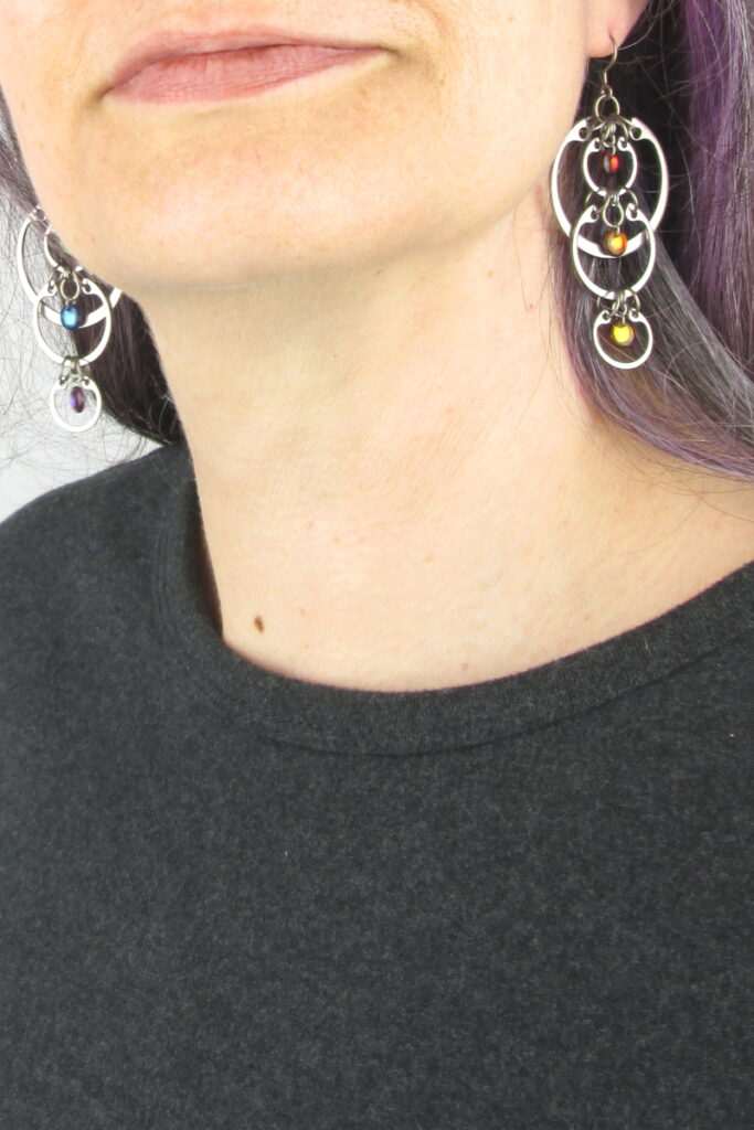 Cropped photo of artist Kelly Jones wearing Wraptillion's modern linked circle Cascading Rainbow Earrings with a dark gray top.