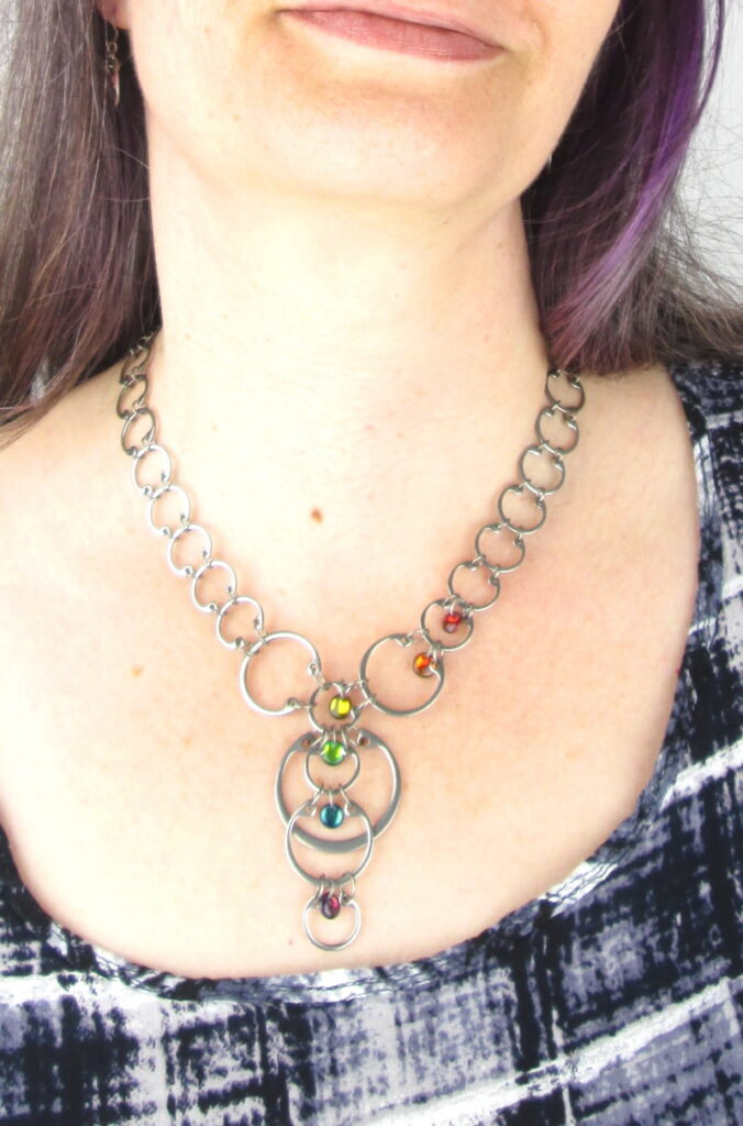 Close cropped modeled photo of Wraptillion's Cascading Rainbow Circles Necklace, worn with a black and white top