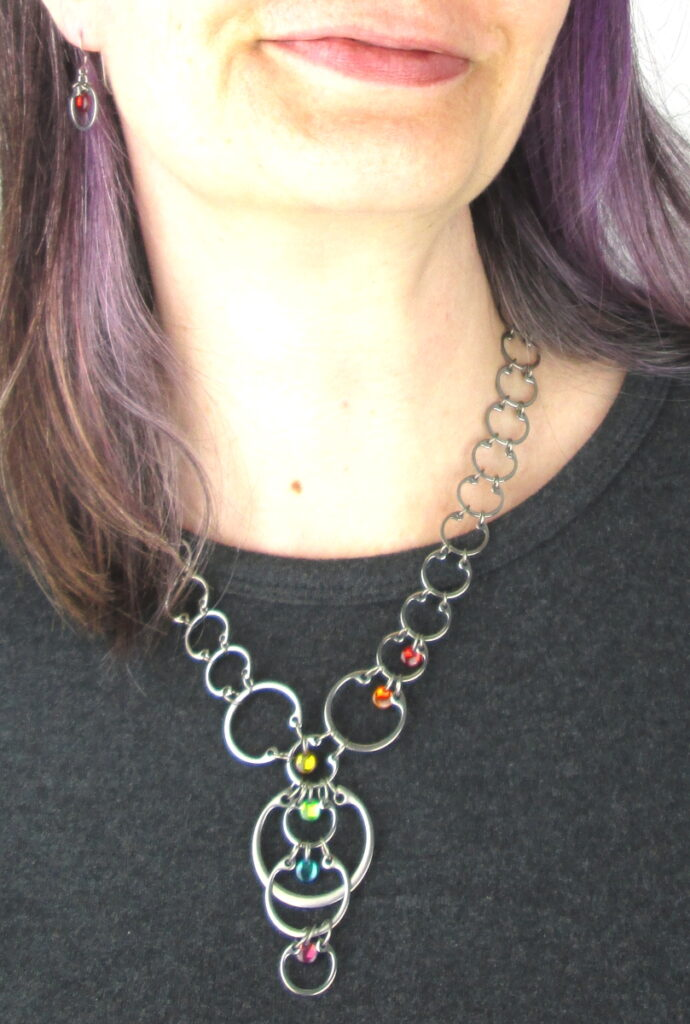Close cropped modeled photo of Wraptillion's Cascading Rainbow Circles Necklace, worn with a dark gray top