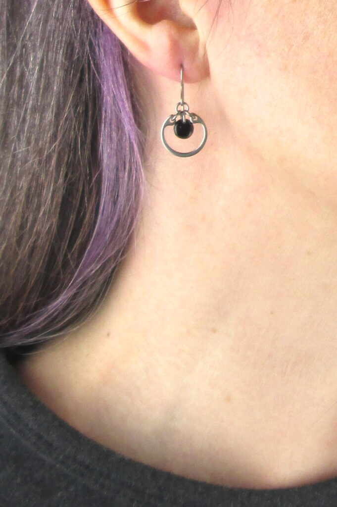 closeup photo of one of Wraptillion's small modern silver-tone circle earrings in black modeled