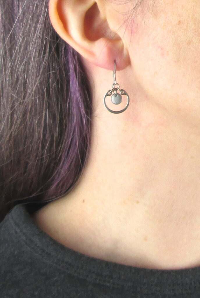 closeup photo of one of Wraptillion's small modern silver-tone circle earrings in gray modeled