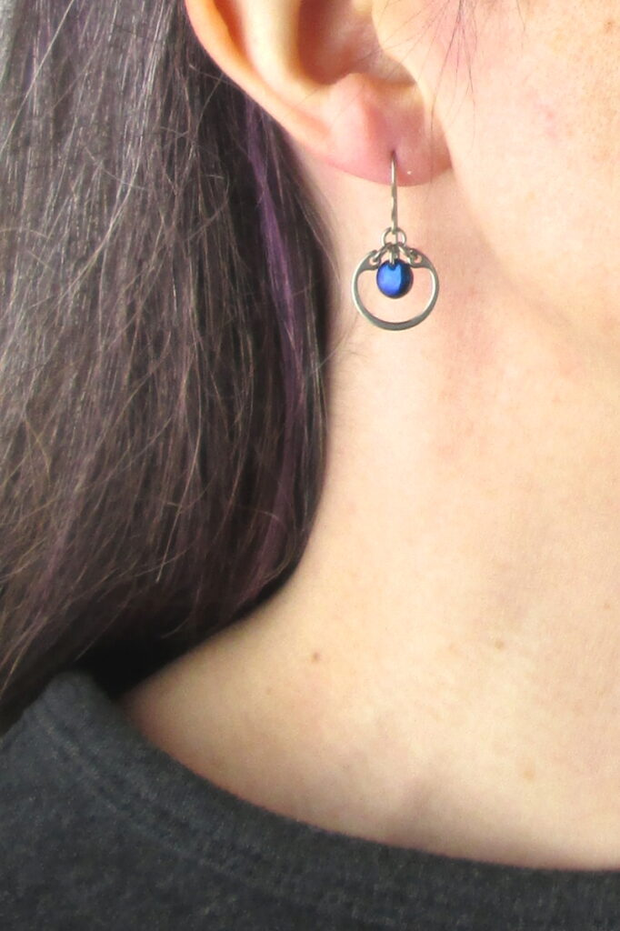 closeup photo of one of Wraptillion's small modern silver-tone circle earrings in navy blue modeled