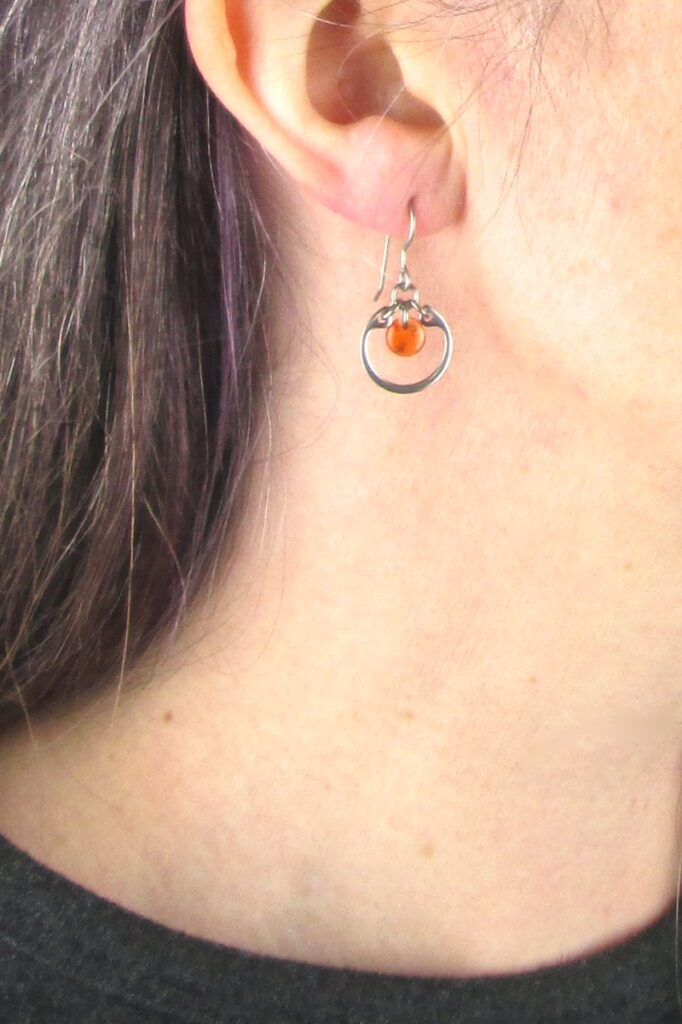 closeup photo of one of Wraptillion's small modern silver-tone circle earrings in orange modeled
