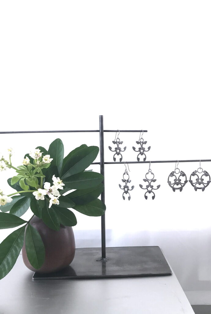Choisya ternata (Mexican Orange Blossom) flowers and leaves in a small modern bud vase, with Wraptillion's Trellis Earrings, Garland Earrings, and Rose Window Earrings.