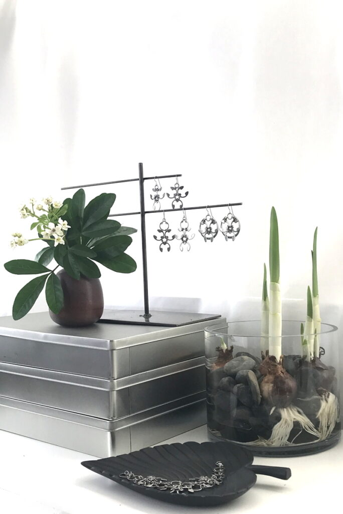 Choisya ternata flowers and leaves in a small modern bud vase on a stack of metal boxes, next to Wraptillion's Trellis Earrings, Garland Earrings, and Rose Window Earrings. Paperwhite narcissus are growing amid rocks in a glass vase. A black leaf dish holds the Garland Bracelet. A sneak peek into Wraptillion's studio.