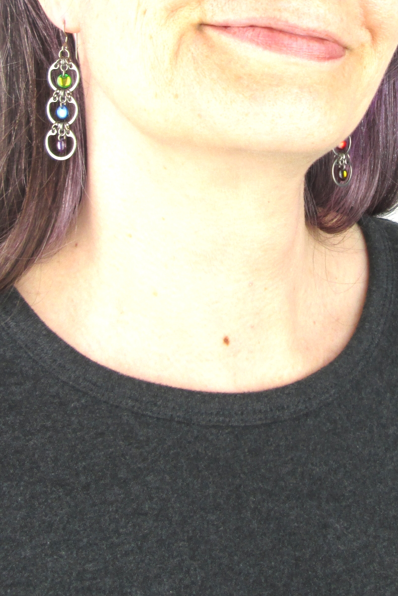 Close cropped modeled photo of Wraptillion's Tripled Rainbow Earrings with a dark gray top