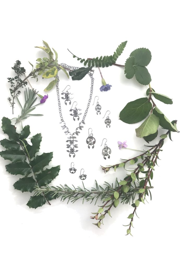 Botanical-inspired jewelry from Wraptillion's Mechanical Garden collection, surrounded by branches from mahonia, salal, rosemary, and other evergreen plants, with snowdrop, primrose, and violet spring flowers.