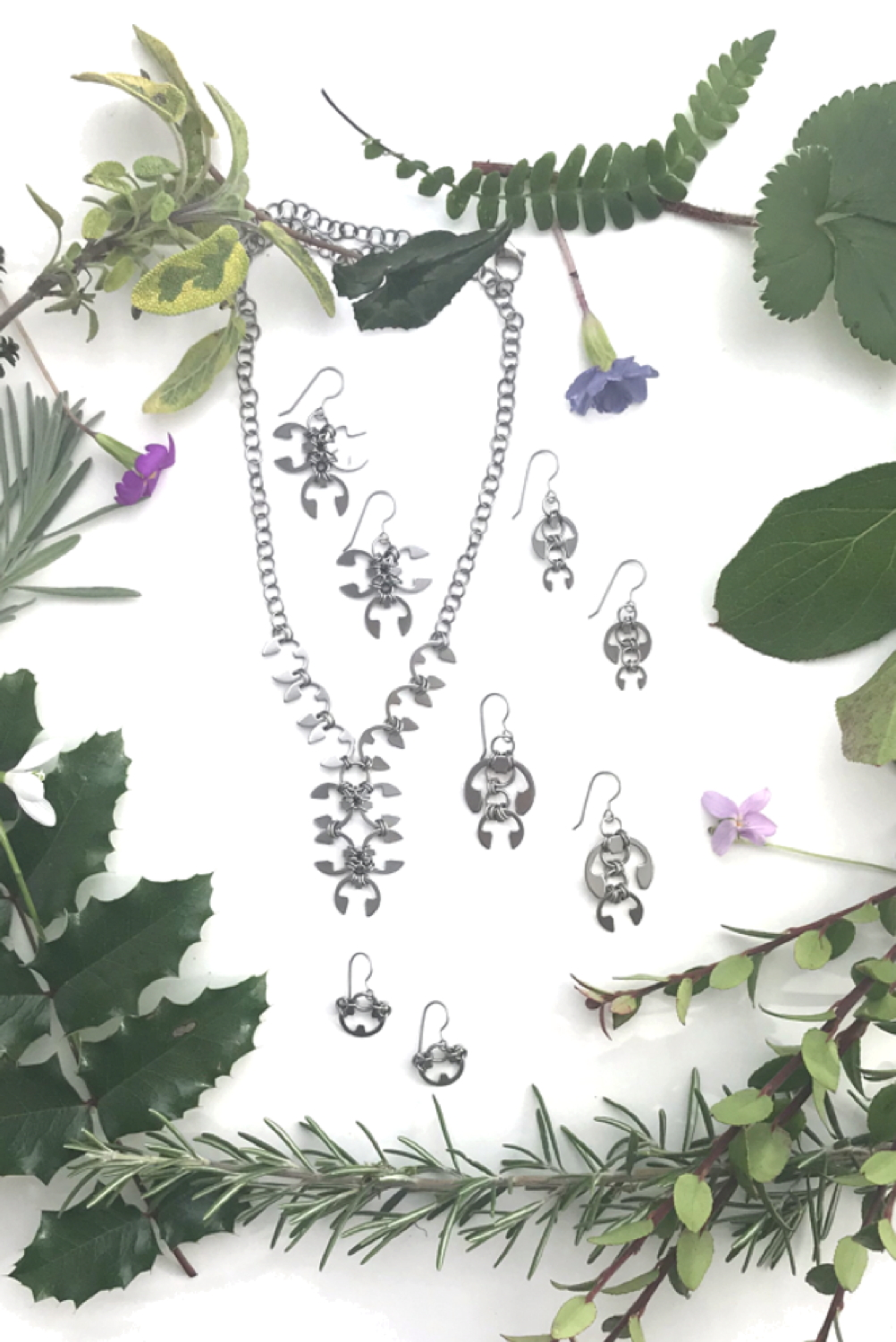 Closeup of botanical-inspired jewelry from Wraptillion's Mechanical Garden collection, surrounded by branches from mahonia, salal, rosemary, and other evergreen plants, with snowdrop, primrose, and violet spring flowers.