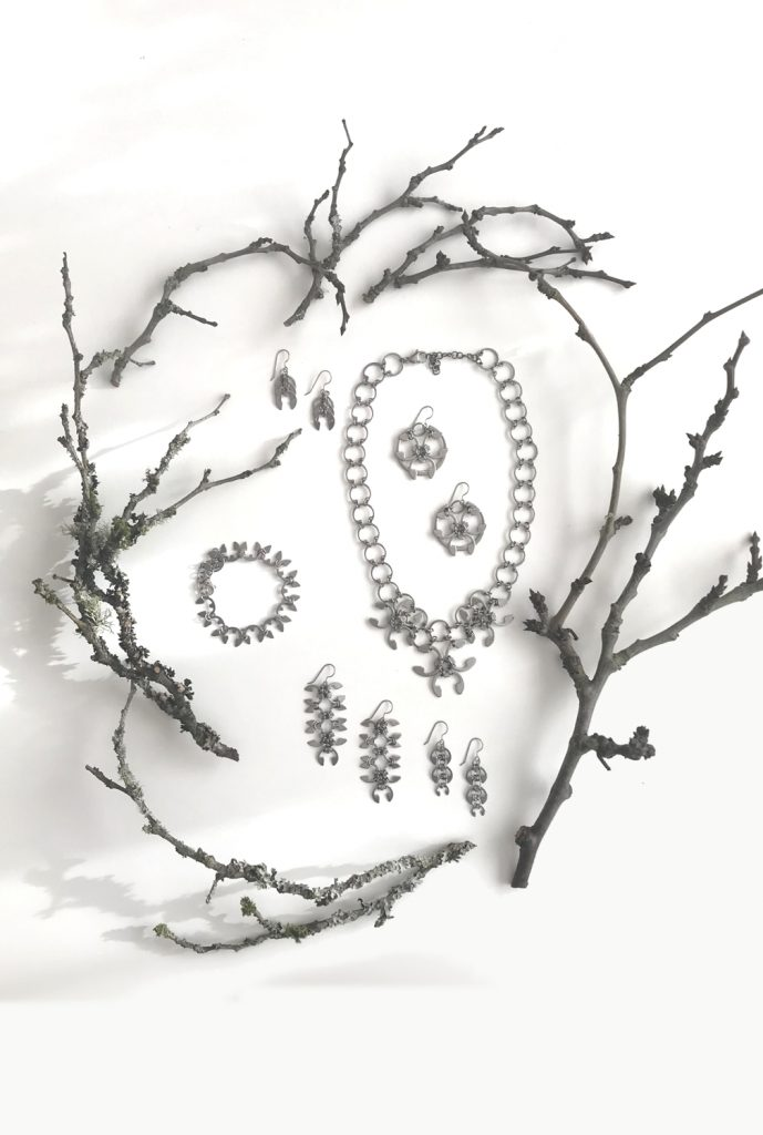 Botanical-inspired jewelry from Wraptillion's Mechanical Garden collection, surrounded by bare plum branches in winter.