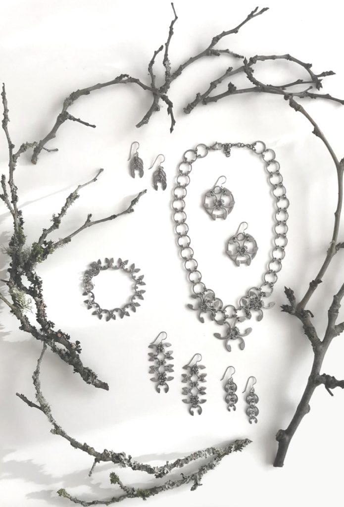 Closeup of botanical-inspired jewelry from Wraptillion's Mechanical Garden collection, surrounded by bare plum branches in winter.