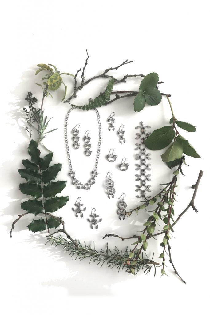 Botanical-inspired jewelry from Wraptillion's Mechanical Garden collection, surrounded by branches from plum, mahonia, salal, rosemary, and other evergreen plants.in winter.