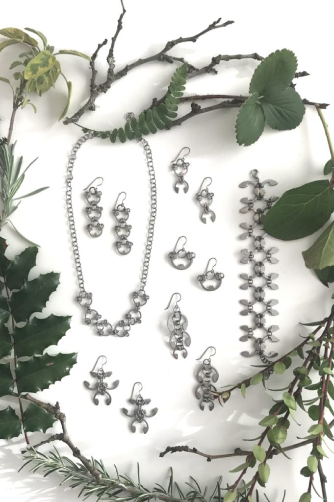 Closeup of botanical-inspired jewelry from Wraptillion's Mechanical Garden collection, surrounded by branches from plum, mahonia, salal, rosemary, and other evergreen plants.in winter.