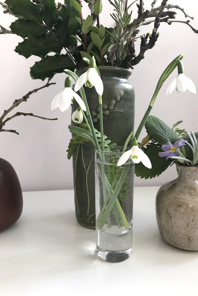 cut snowdrops in a small glass vase with a fern frond, shown in front of other small winter floral arrangements