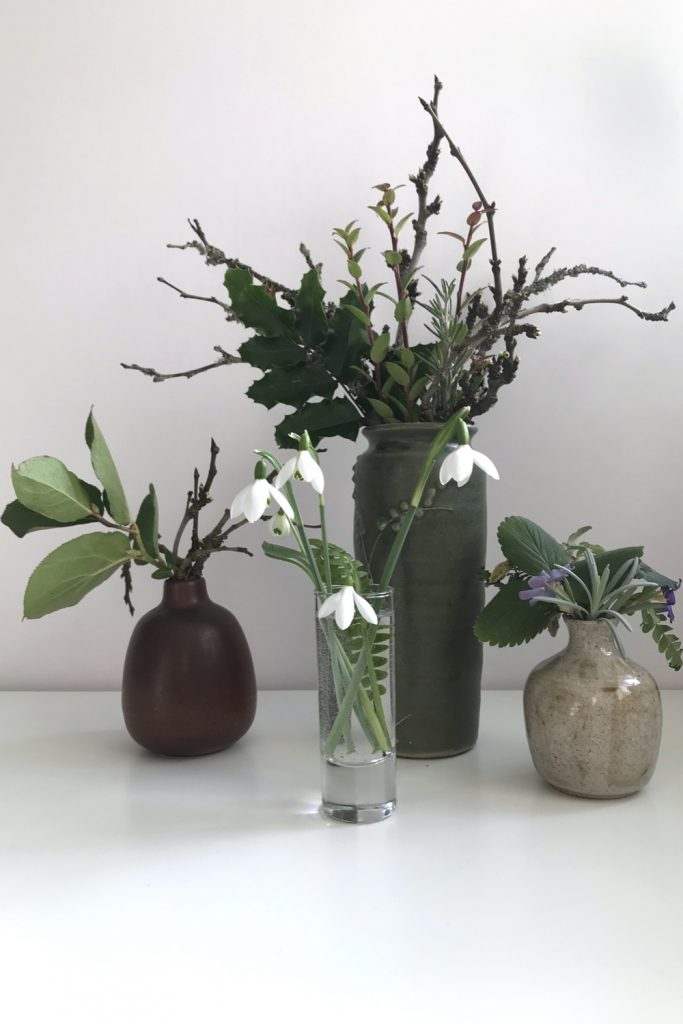 cut snowdrops in a small glass vase with a fern frond, shown in front of 3 other small winter floral arrangements