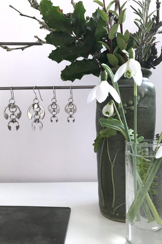 cut snowdrops in a small glass vase with a fern frond, shown in front of another small winter floral arrangement and Wraptillion's Hops Earrings and Short Fuchsia Earrings