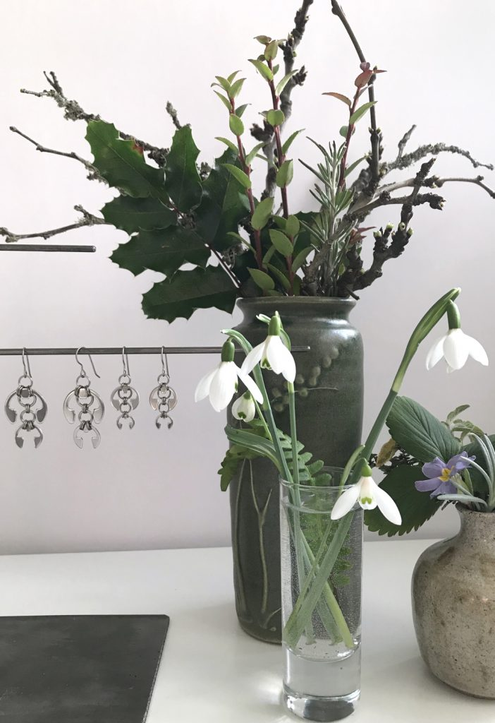 cut snowdrops in a small glass vase with a fern frond, shown in front of other small winter flower arrangements and Wraptillion's Hops Earrings and Short Fuchsia Earrings