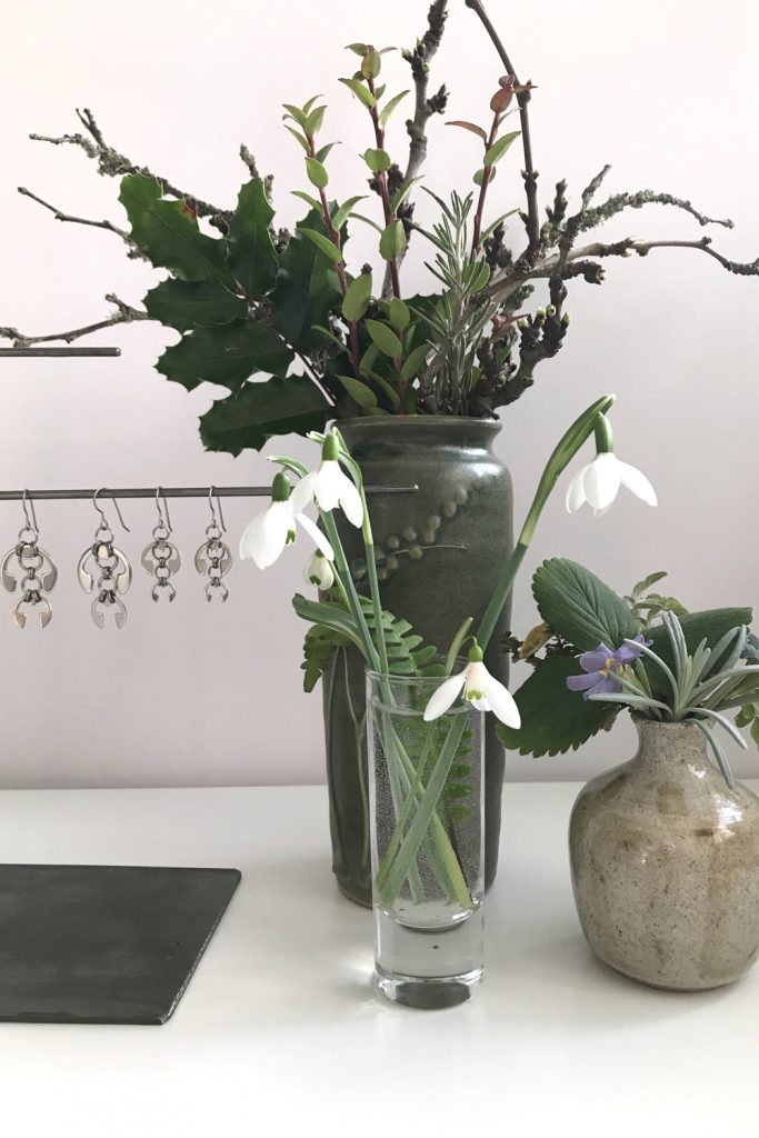 cut snowdrops in a small glass vase with a fern frond, shown in front of other small winter leaf, branch, and flower arrangements and Wraptillion's Hops Earrings and Short Fuchsia Earrings