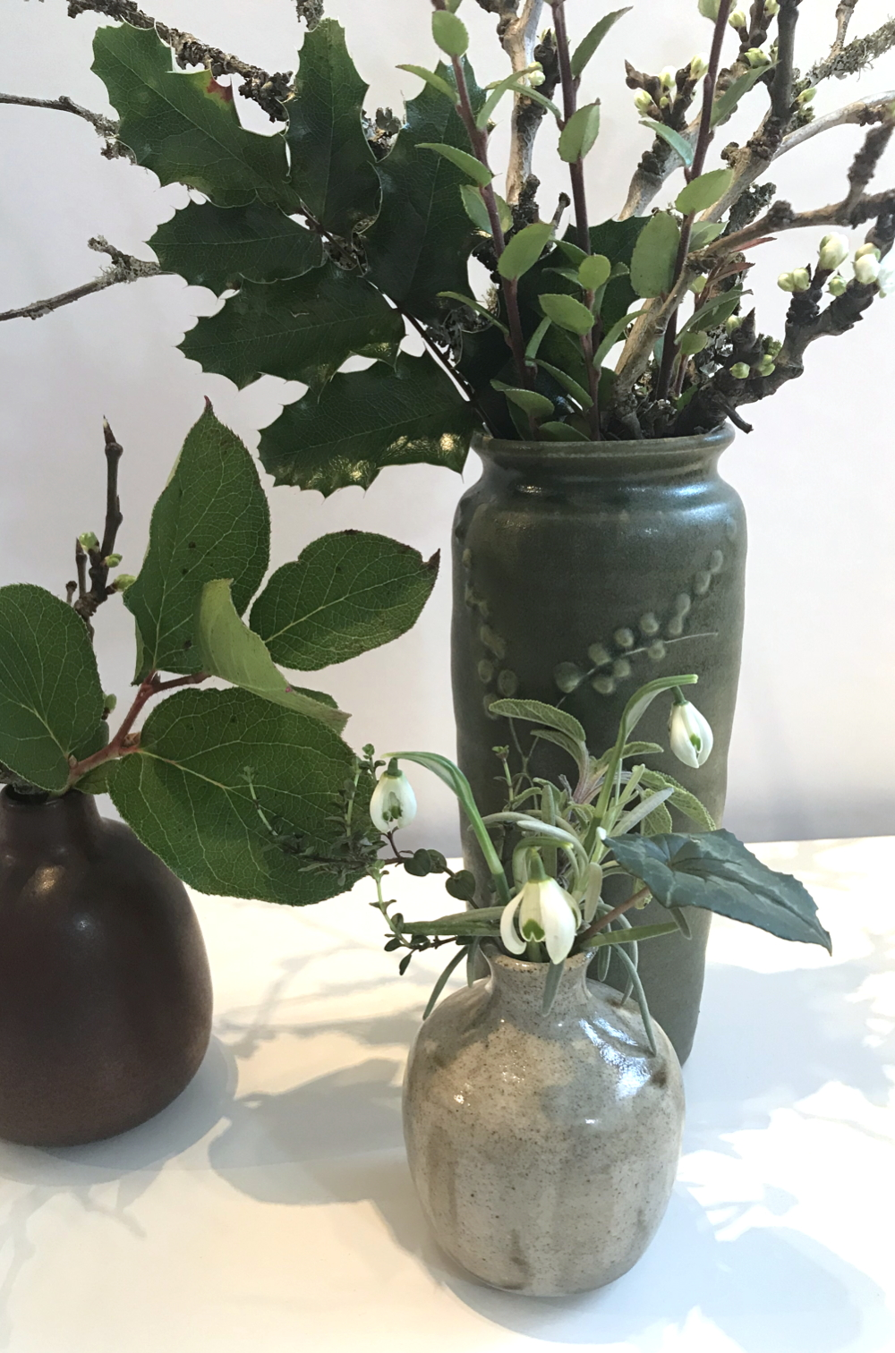 Photo of three small winter flower arrangements in ceramic vases, with salal, mahonia, plum branches breaking into flower, and double snowdrops.