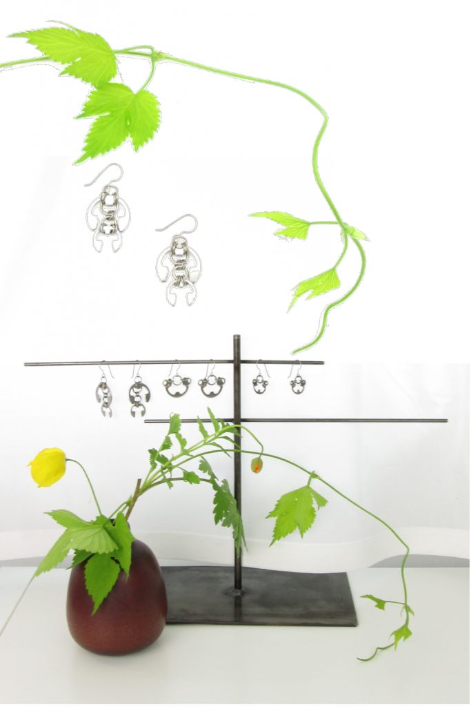 Complied image of hop vines, cut yellow Welsh poppies and hops vines in a small bud vase, and Wraptillion's Hops Earrings and Small and Large Poppies Earrings on a jewelry stand