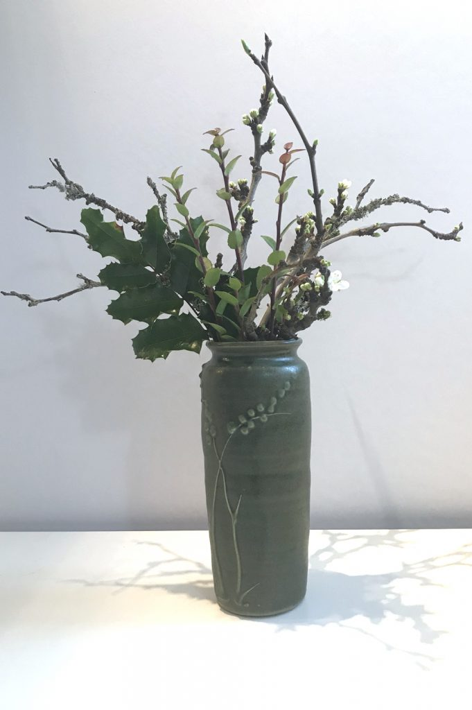 Photo of a small casual winter floral arrangement in a green ceramic vase, with mahonia, evergreen huckleberry, and plum branches breaking into flower.