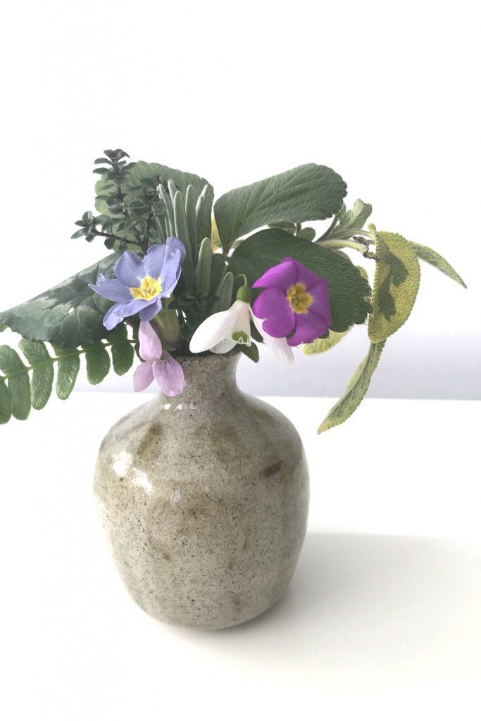 Wraptillion's studio flowers: a small everyday winter flower arrangement with strawberry, thyme, sage, lavender, fern, primrose, snowdrop, & violet, in a small beige handmade ceramic vase.