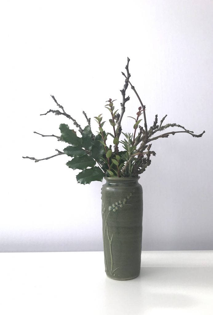 Waptillion's studio flowers: a small everyday winter flower arrangement, featuring bare plum branches and evergreen huckleberry, mahonia, and rosemary leaves, in a handmade green ceramic vase.
