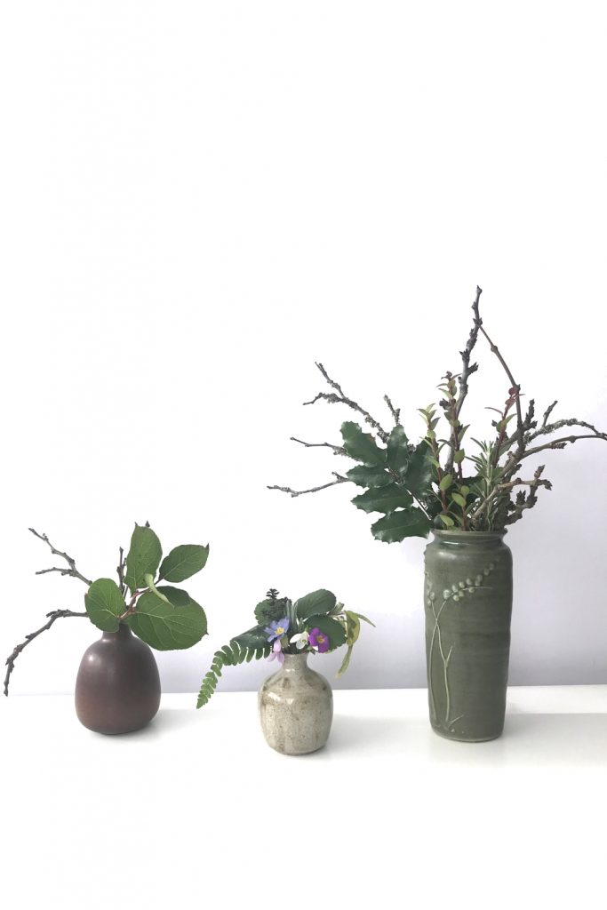 Three small everyday winter flower arrangements, featuring bare plum branches, evergreen leaves such as salal and mahonia, and a few early spring flowers like primrose, snowdrop, and violet, all in ceramic vases.
