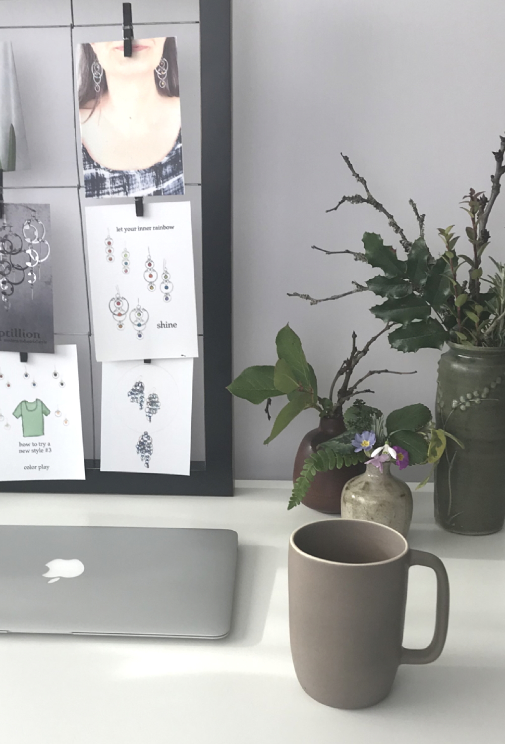 A glimpse into Wraptillion's studio workspace: laptop, mug, three small everyday winter flower arrangements, and the corner of a moodboard.