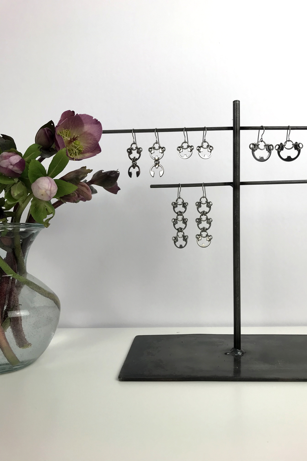 Cut pink hellebores in a glass vase, with Wraptillion's Scarab Earrings, Lotus Earrings, Small Poppy Earrings, and Large Poppy Earrings.