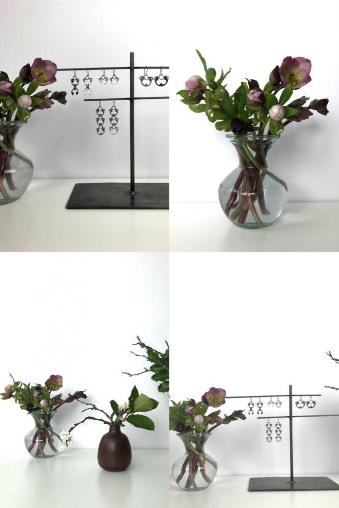 Four images showing small casual winter flower arrangements: pink hellebores in a glass vase, flowering plum branches and salal leaves in a brown bud vase, plum branches, mahonia, and huckleberry leaves, and Wraptillion's Scarab Earrings, Lotus Earrings, Small Poppy Earrings, and Large Poppy Earrings.