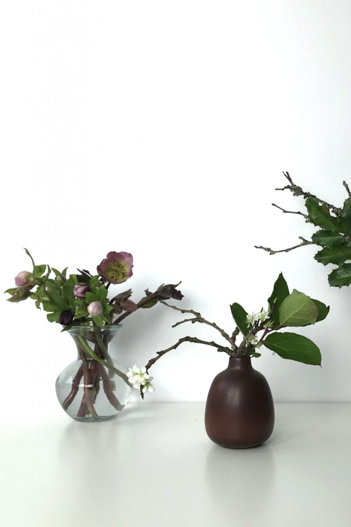 Three small casual winter flower arrangements: pink hellebores in a glass vase, flowering plum branches and salal leaves in a brown bud vase, plum branches, and mahonia leaves.