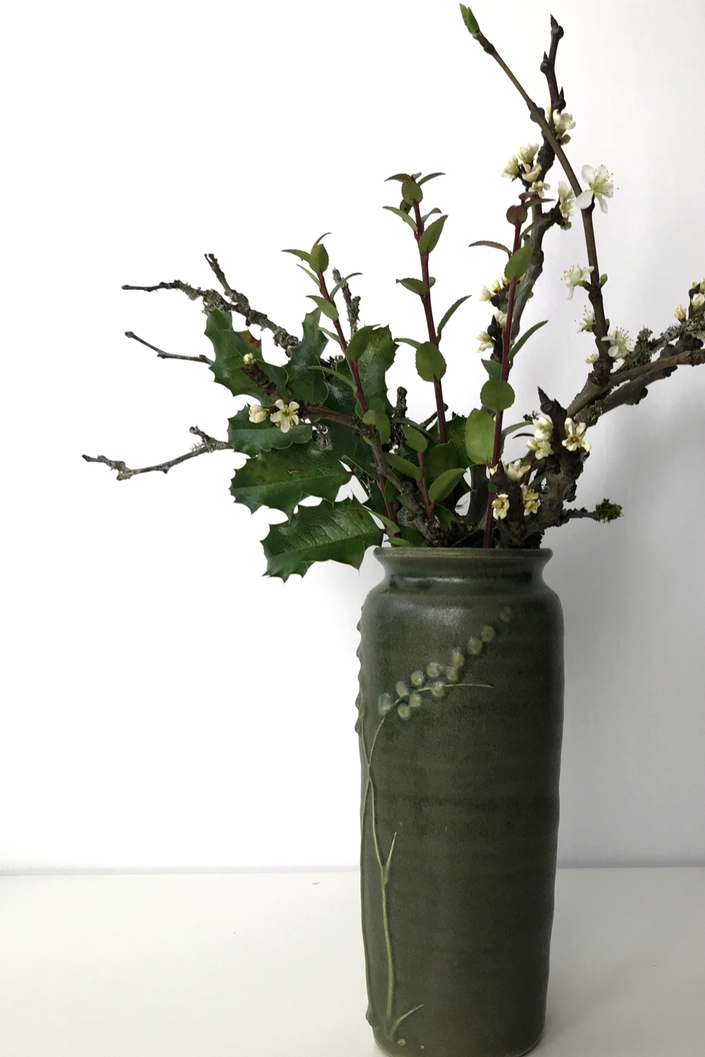 A small winter arrangement of plum branches in bloom with mahonia and huckleberry leaves in a green ceramic vase.