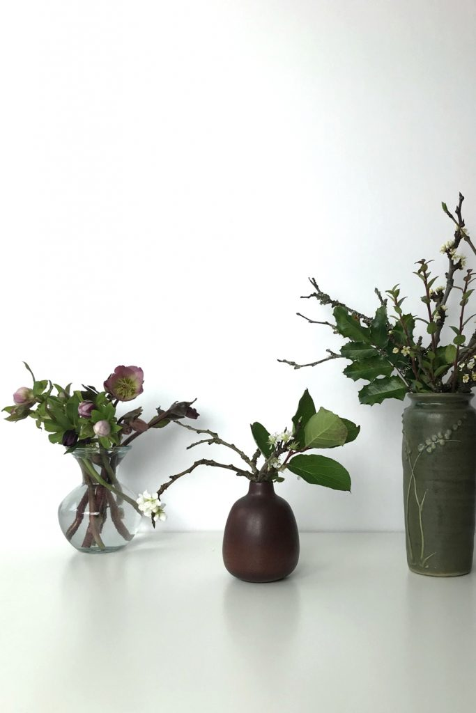 Three small casual winter flower arrangements: pink hellebores in a glass vase, flowering plum branches and salal leaves in a brown bud vase, plum branches, mahonia, and huckleberry leaves in a green vase.