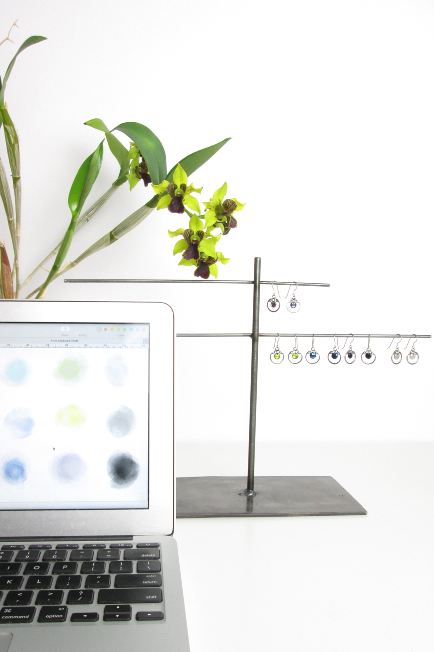 My studio workspace, with open laoptio displaying a color paletter, orchid Dendrobium 'Green Flash,' and a variety of Wraptillion's Small Circle Earrings in various colors hanging on a jewelry stand..