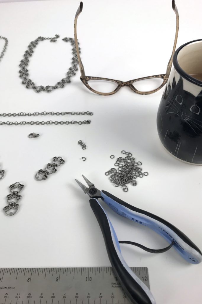 Kelly Jones of Wraptillion's studio workspace, with the Delicate Lotus Necklace in progress, shown with pliers, reading glasses, and a mug of tea.
