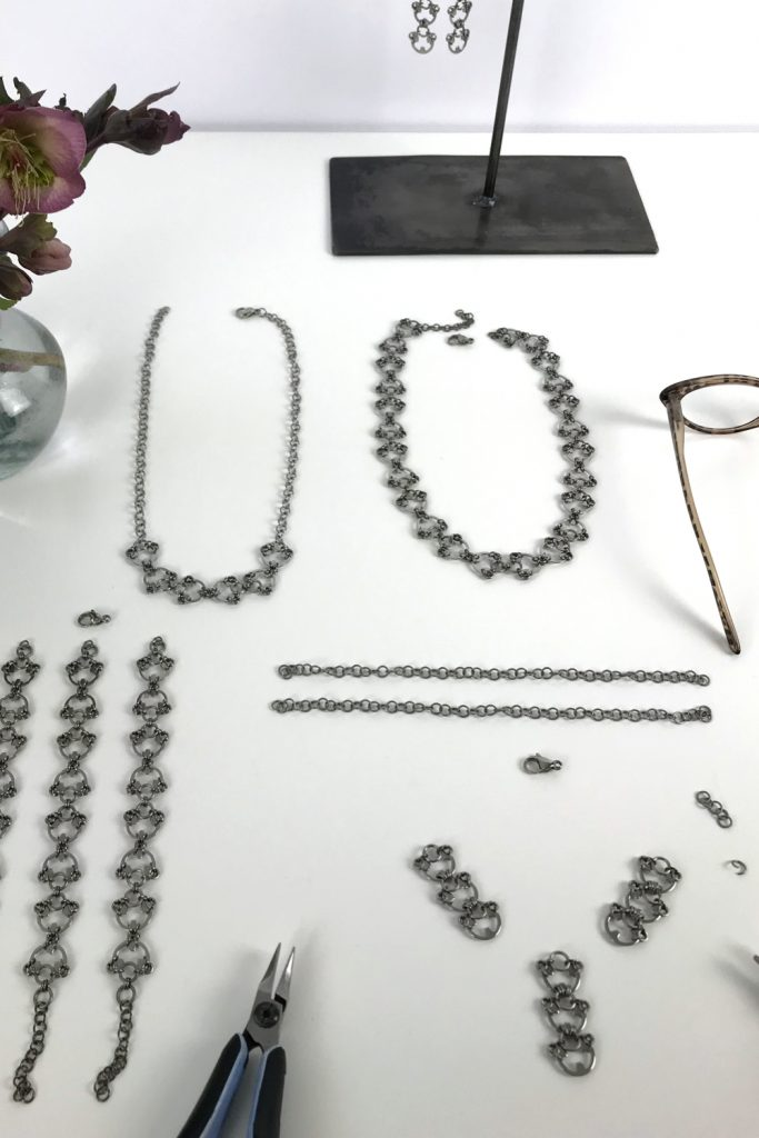 Kelly Jones of Wraptillion's studio workspace, with the Delicate Lotus Necklace in progress, shown with pliers, reading glasses, the Scarab Necklace, Delicate Scarab Necklace, Scarab Bracelets, and Lotus Earrings.