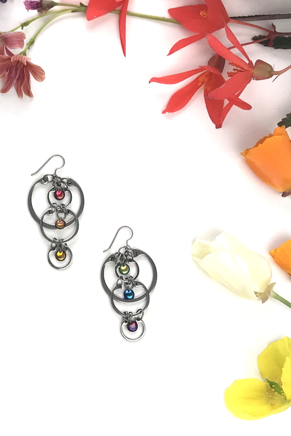 Wraptillion's modern Cascading Rainbows Earrings in a flatlay next to yellow Welsh poppies, cream and orange California poppies, red begonias, and coral lewisia flowers.