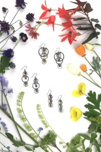 Wraptillion's Cascading Rainbows Earrings, Alternating Rainbows Earrings, and Tripled Rainbow Earrings amid a botanical rainbow of flowers, including: red begonias, orange, cream, and yellow poppies, green hellebores, primroses, and fringe flowers, bluebells and forget-me-nots, purple columbines and primroses, and coral lewisia, in a visually satisfying flatlay.